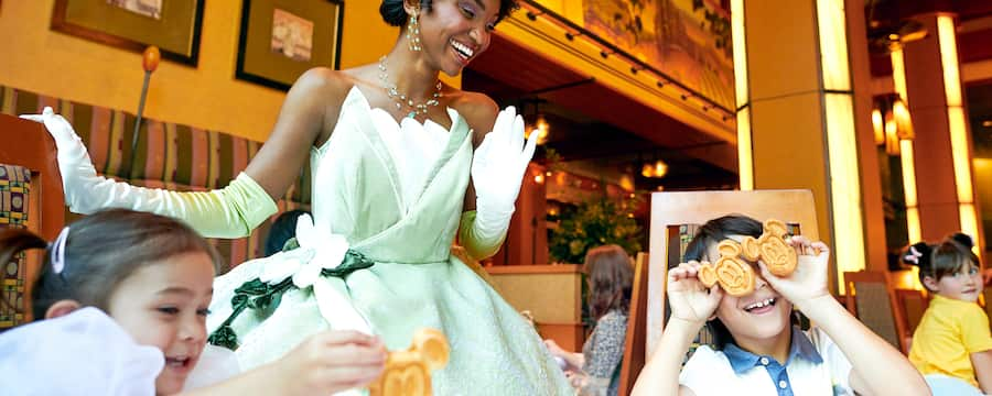 Princess Tiana laughs, watching 2 little kids play with their food in a restaurant