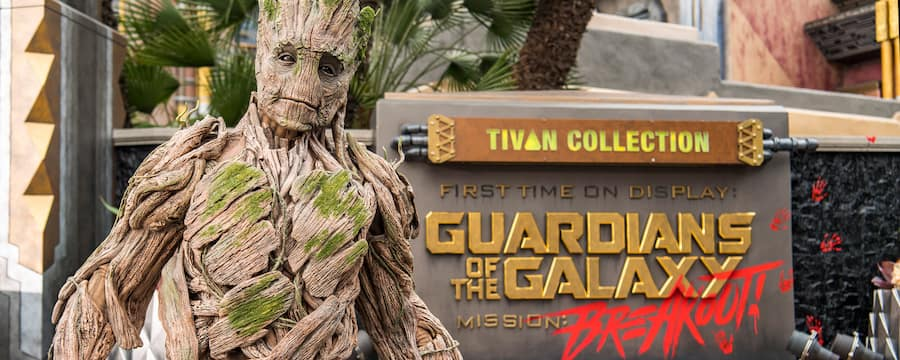 Groot stands in front of the sign for Guardians of the Galaxy – Mission: Breakout