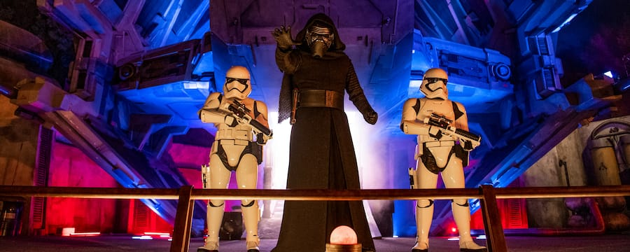 With one arm outstretched, Kylo Ren stands in front of his TIE assault shuttle alongside 2 stormtroopers at Star Wars Galaxys Edge