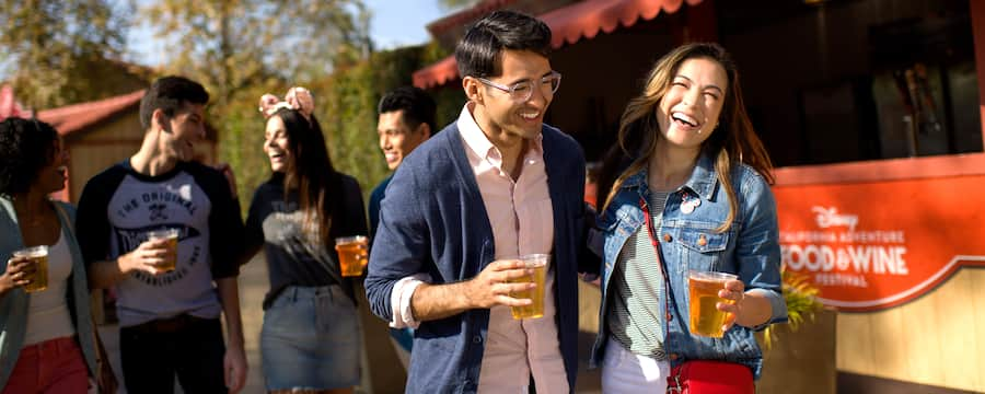 A couple, carrying their beers and laughing together in front of a craft brew cart