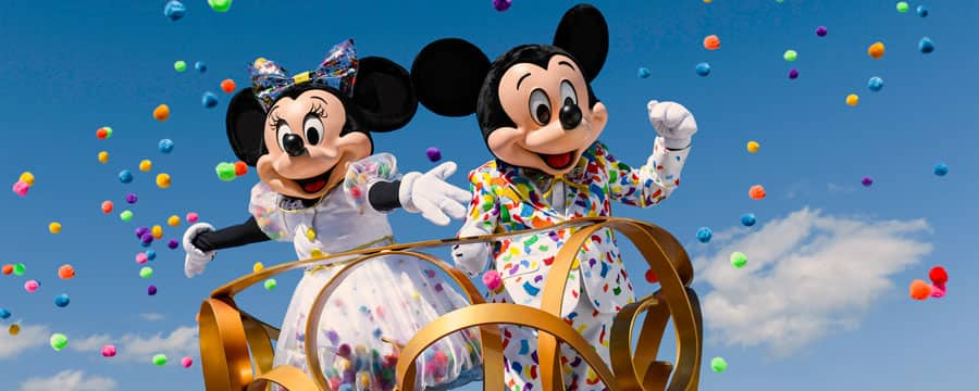 Dressed festively, Mickey Mouse and Minnie Mouse wave from an ornate platform