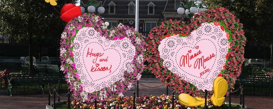 A flower garden with 2 gigantic, heart shaped valentines, autographed by Minnie Mouse