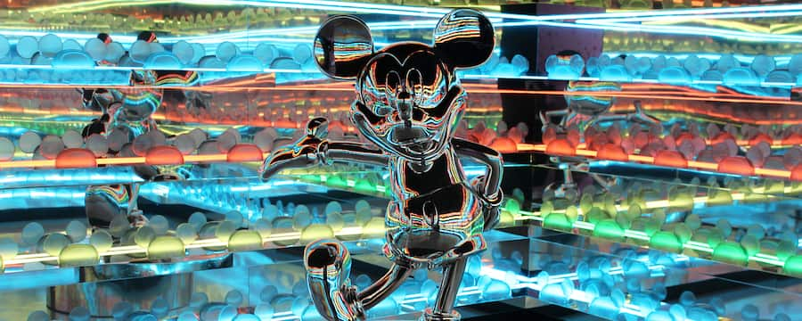 A metallic statue of Mickey Mouse in a room with mirrors and coloured lights