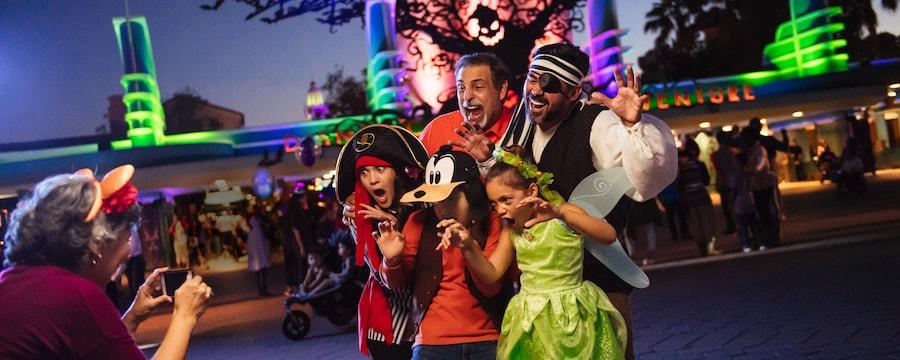 Cerca de la entrada de Disney California Adventure Park, un abuelo, un papá y sus 3 hijos con disfraces de Halloween posan para la abuela con Oogie Boogie y murciélagos que vuelan por encima.