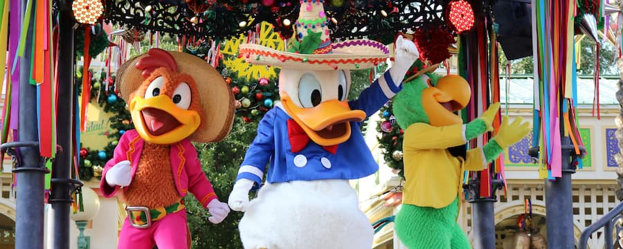 Amidst holiday décor, Donald Duck waves while standing on stage with Panchito and José during Viva Navidad, a celebration of Latino holiday traditions
