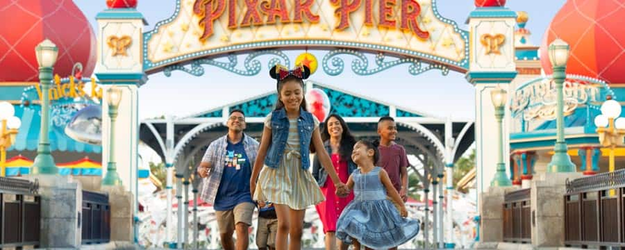 2 little girls hold hands and walk in front of their family across Pixar Pier