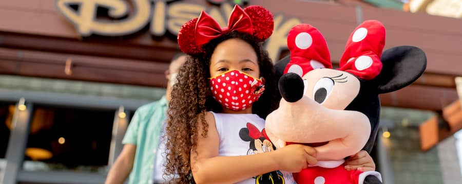 A young girl with Minnie-themed facemask and mouse ears, holding a large Minnie plush