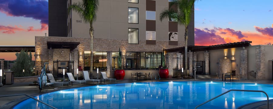 A pool area with tables, chairs, plants and trees outside the SunCoast Park Hotel Anaheim