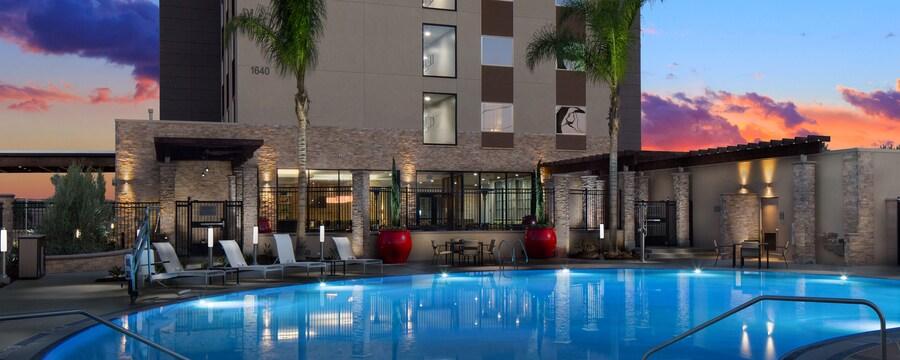 Un área de piscina con mesas, sillas, plantas y árboles fuera de SunCoast Park Hotel Anaheim