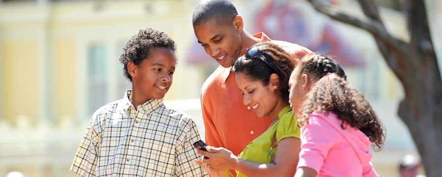 A family huddles around a mobile device at Disneyland Resort
