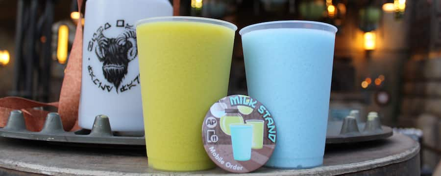 A button saying Milk Stand in front of glasses of green and blue milk