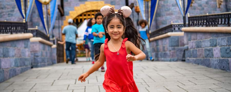 A smiling young girl with glistening mouse ears walks across the bridge leading from Sleeping Beauty Castle