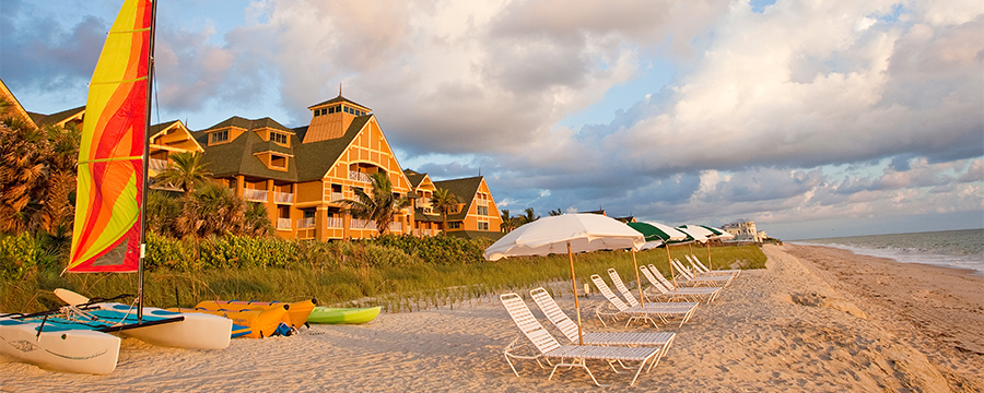 A beach with lounge chairs, umbrellas and rental boats, and the Resort behind