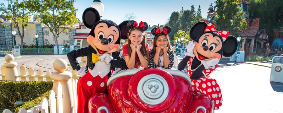 Dos niñas con orejas de Mickey están sentadas en un auto Toontown y posan con Mickey y Minnie