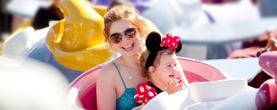 Una mamá sonriente monta la atracción Dumbo the Flying Elephant con su hija vestida con un traje de Minnie Mouse