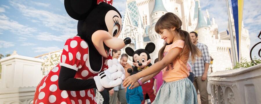 Fuera del Castillo de la Bella Durmiente, Minnie saluda a una niña mientras Mickey entretiene a su familia