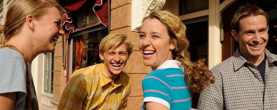 Una mujer, su esposo y 2 niños adolescentes ríen mientras están de pie fuera de un edificio