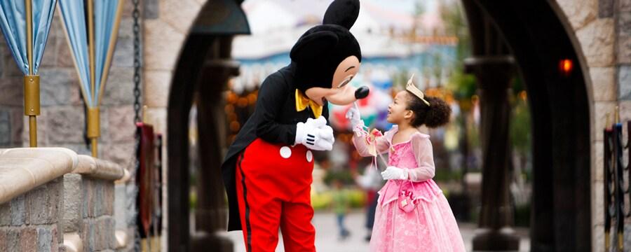 Una niña vestida de Princess Aurora toca a Mickey bajo un arco que conduce a Fantasyland