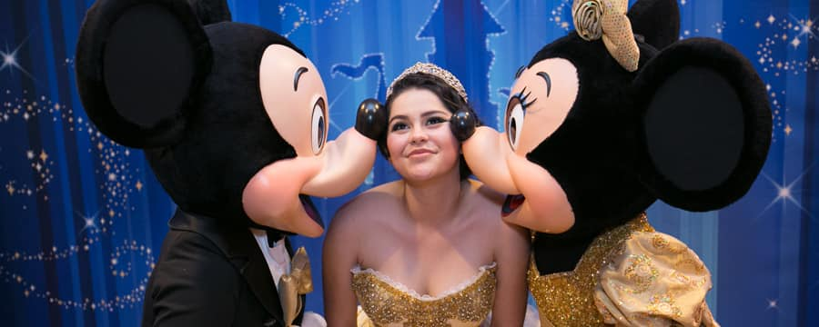 A smiling young woman in a quinceañera gown and tiara bends to let Mickey and Minnie Mouse plant a kiss on each of her cheeks