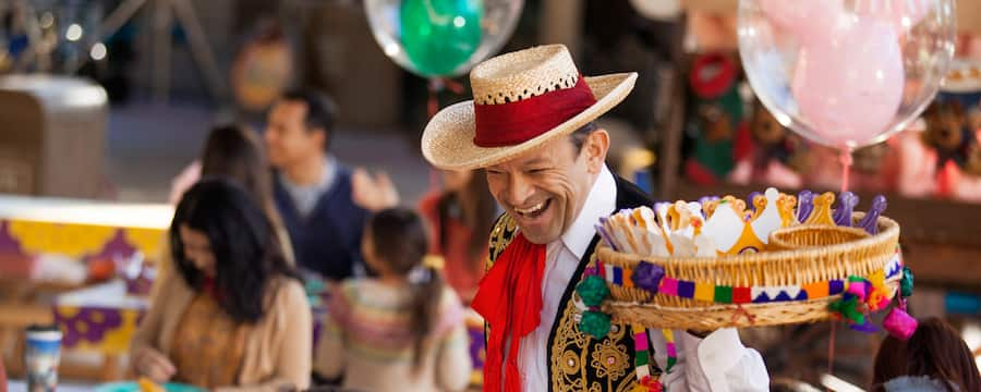 En una celebración de Día de los Reyes, un hombre con un atuendo festivo de estilo latinoamericano sostiene una charola con coronas de papel