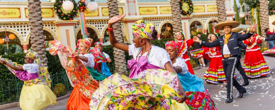 Female dancers in floral turbans and patterned skirts lead a lively procession that includes men and women in traditional Mexican dress
