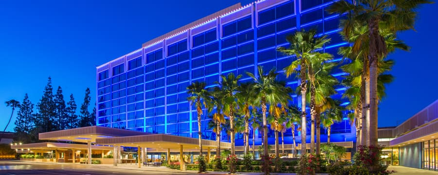 Flanked by palm trees, the modern façade of the Disneyland Hotel glistens against the night sky