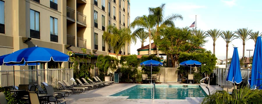 Lounge chairs and umbrellas line the pool at Hampton Inn & Suites