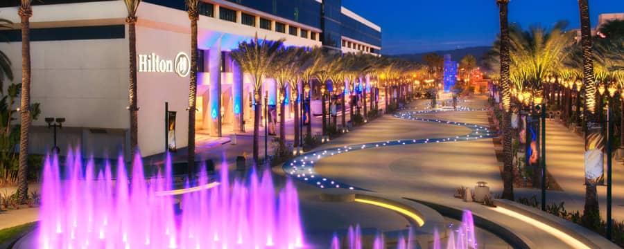 Una fuente centelleante y un arroyo sinuoso en Hilton Anaheim iluminados en la noche