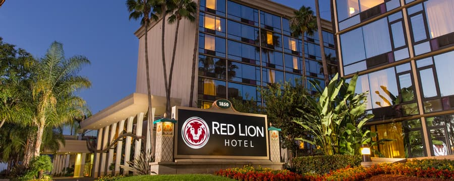A manicured garden around the sign and entrance to the Red Lion Hotel Anaheim lit up at night