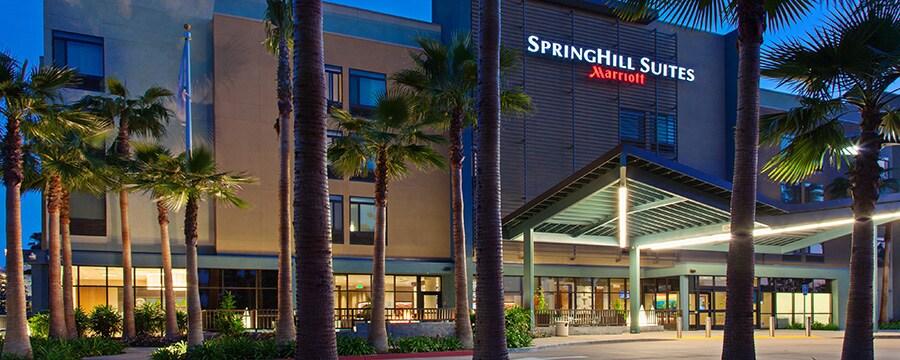 El exterior de Springhill Suites de noche rodeado de palmeras