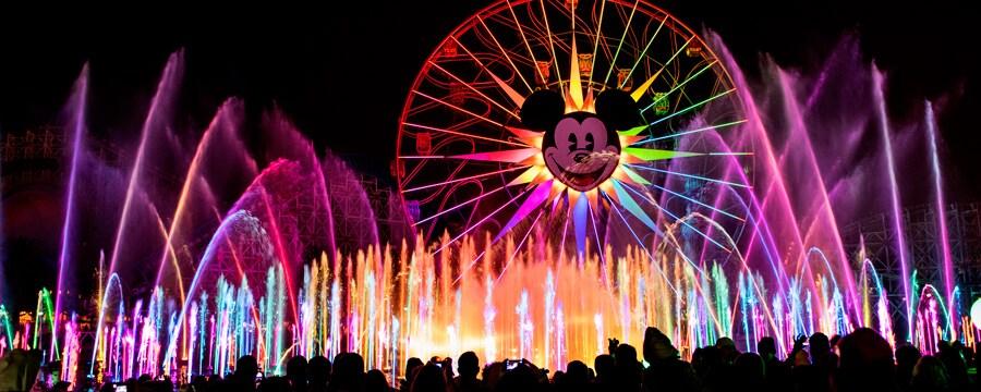 Las fuentes, los láseres y las proyecciones del espectáculo nocturno World of Color iluminan el cielo por la noche