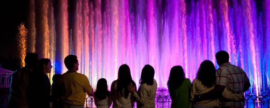 Visitantes ubicados en un área preferencial de observación miran el espectáculo World of Color