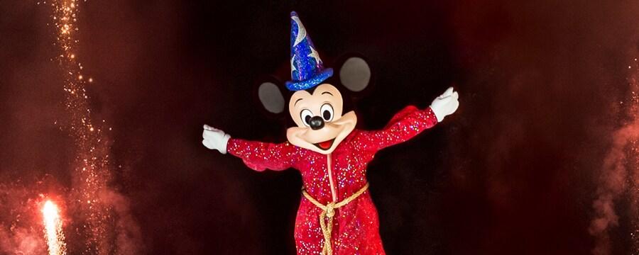 Sorcerer Mickey sonriendo mientras las chispas vuelan por el cielo nocturno durante una presentación de Fantasmic!