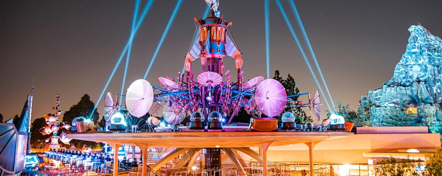 Spotlights crisscross the night sky from atop the Observatron in Tomorrowland with the Matterhorn behind