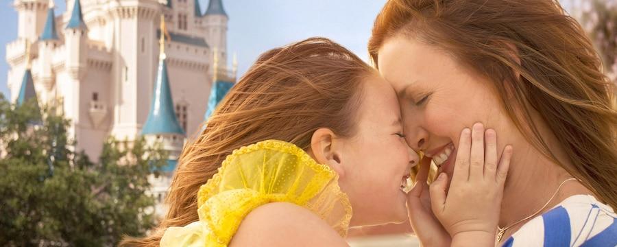 Una madre y su hija dándose un cálido abrazo frente al Cinderella Castle en el Parque Temático Magic Kingdom