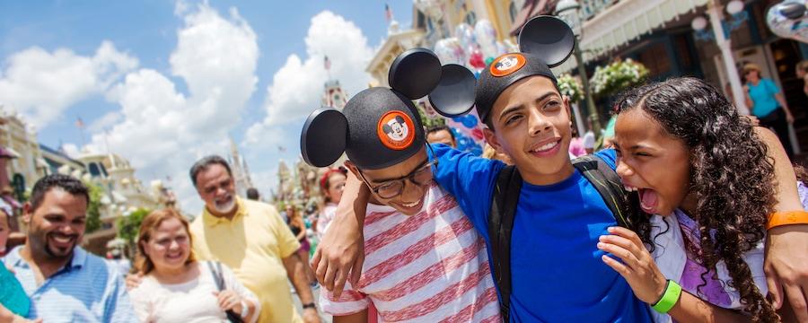 2niños adolescentes y una niña se abrazan y ríen juntos en Walt Disney World Resort, mientras sus padres los observan