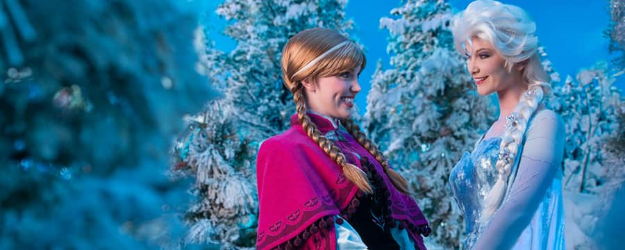 Anna and Elsa hold hands among the icy trees of Arendelle