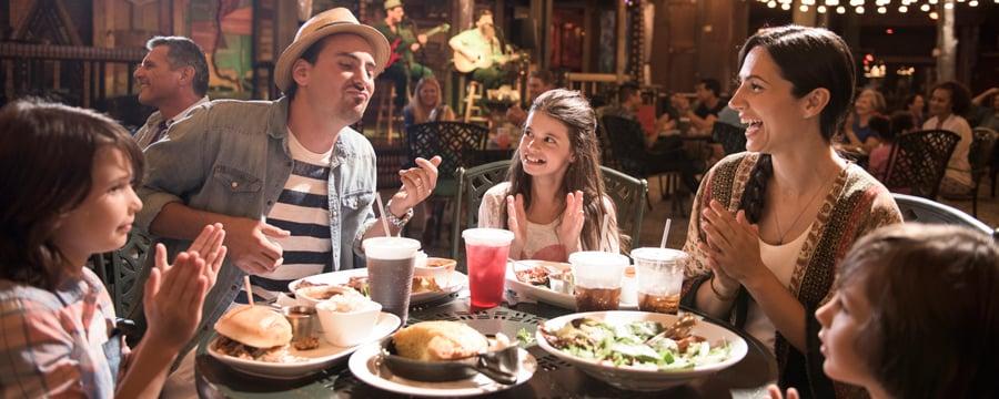 Une famille de 5personnes porte un toast autour d'un dîner de célébration à Disney Springs