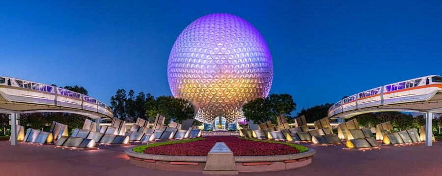 El monorriel pasa por ambos lados del Spaceship Earth mientras el centro emblemático de Epcot se ilumina por la noche