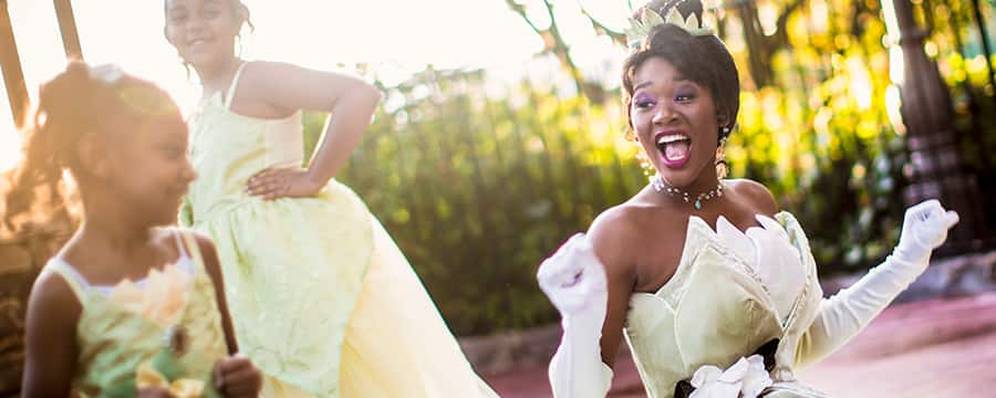 Princess Tiana in a fenced courtyard laughs with 2 girls wearing Princess Tiana costumes