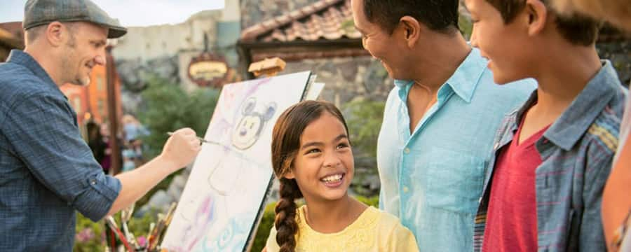 A family smiles as they watch a man paint Mickey Mouse