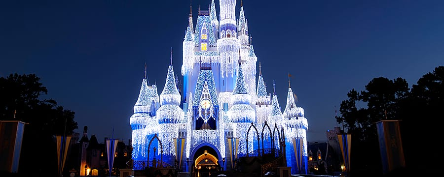 Cinderella Castle shining at nighttime under the glow of millions of glimmering holiday lights