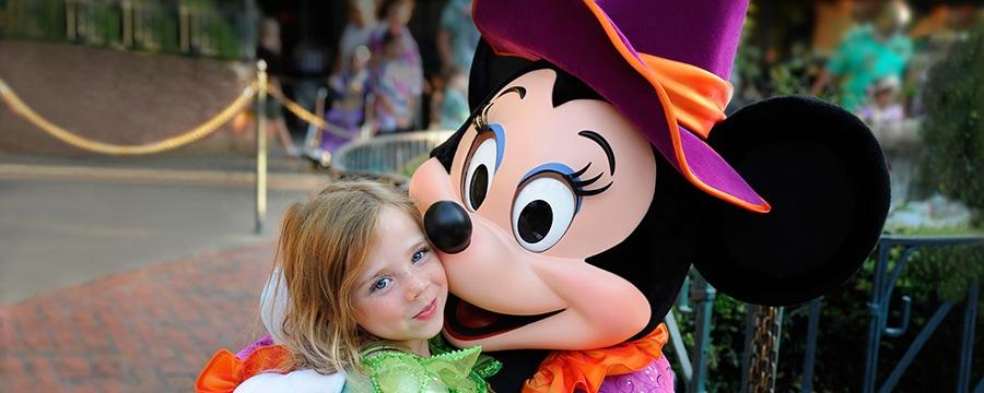 Una Visitante joven vestida como un hada de Disney sonríe mientras conoce a Minnie Mouse vestida con temática de Halloween
