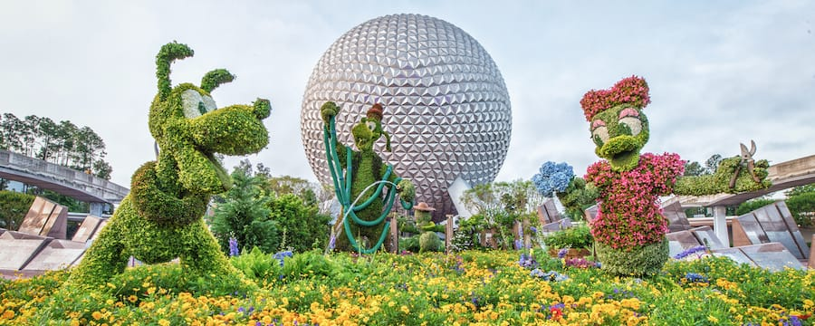 Topiaries of Pluto, Goofy and Daisy Duck on display directly in front of Spaceship Earth at Epcot.