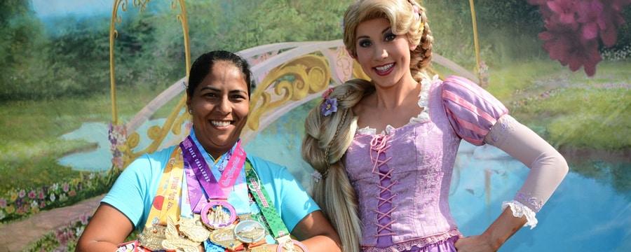 Princesse Aurore de Sleeping Beauty pose à côté d'un marathonien couvert de médailles Disney Race Challenge