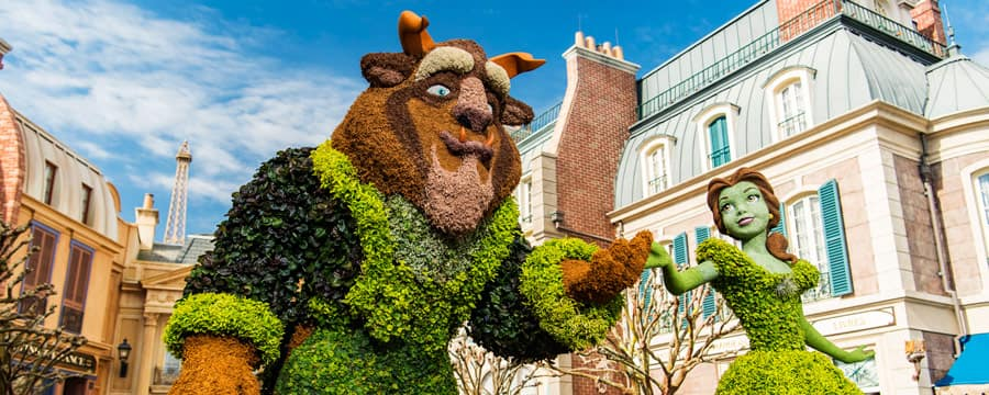 Topiaries of Belle and the Beast near stone buildings