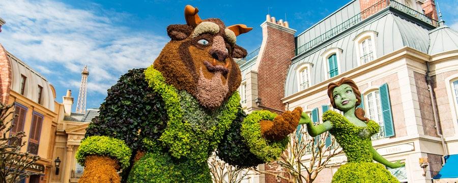 Des topiaires de Beauty and the Beast près de bâtiments en pierre