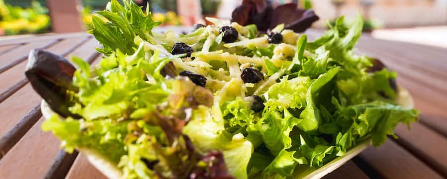 A festive salad of mixed greens garnished with berries and served atop a wooden picnic table