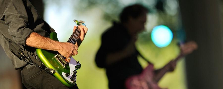 2hombres tocan guitarras en un escenario