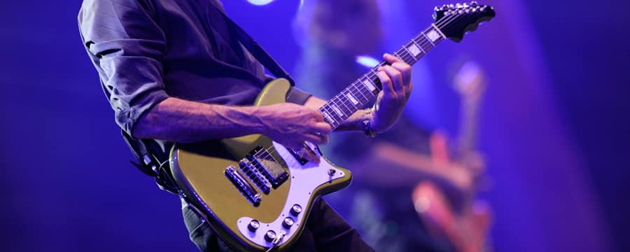 A guitarist performs on stage in the foreground alongside a fellow musician playing a bass guitar